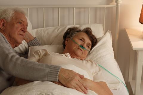 man aan het ziekenbed van een vrouw