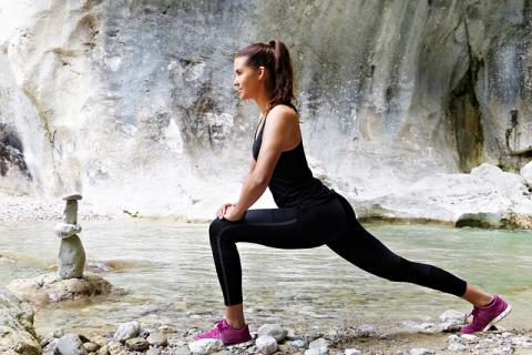 Jonge vrouw die stretchoefeningen doet