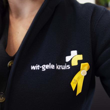 Geel lintje Kom op Tegen Kanker opgespeld bij Wit-Gele Kruis medewerker