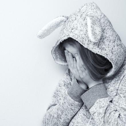 Jong meisje verbergt gezicht achter handen