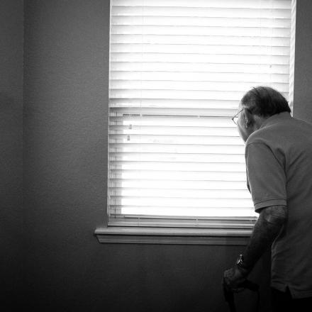 Oude man kijkt uit het raam