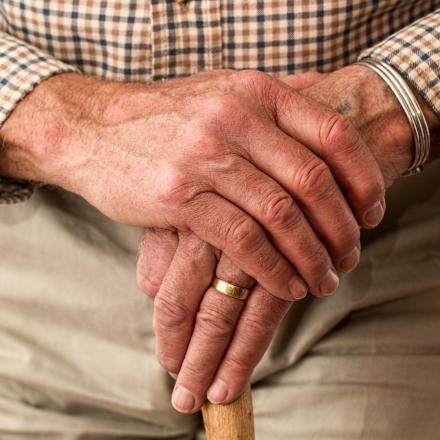 oudere man leunt op wandelstok
