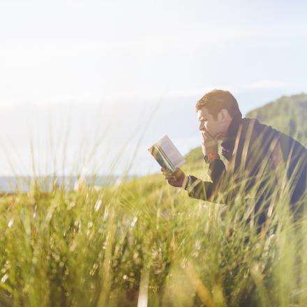 Man leest een boek op een bankje