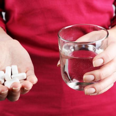 Medicatie in de hand met glas water