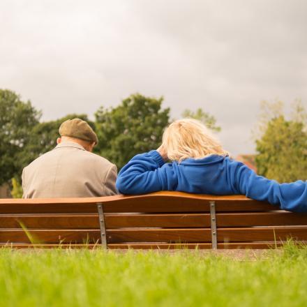 Oude man en vrouw zitten samen op een bankje